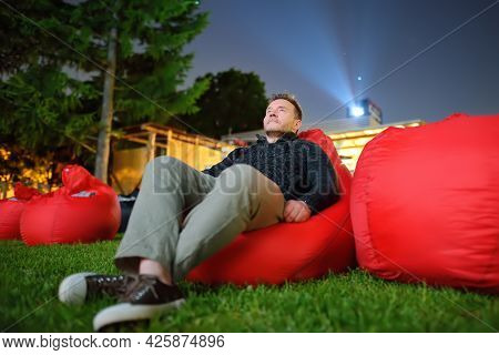 Mature Man Laying On Pillow On Grass And Watching Film At Outdoor Cinema In Public Park. Perfect Spe