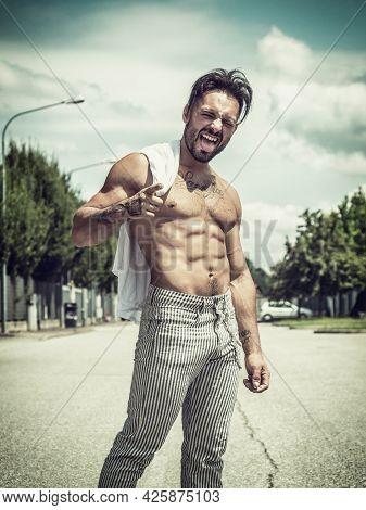Shirtless Muscular Young Man Walking On Urban Street