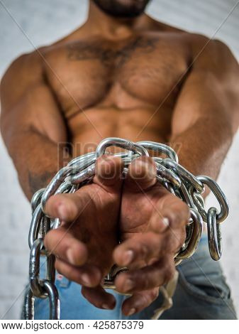 Strong Shirtless Muscular Man Tearing Chains Around Hands