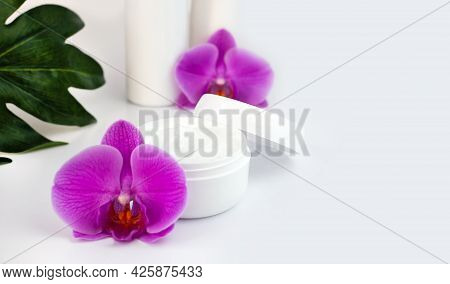 A Jar Of Hands Cream With Orchids On White Background. Natural Skincare Cosmetics. Hand Skin Care Co