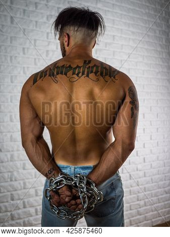 Back Of Strong Shirtless Muscular Man With Chains Around Hands