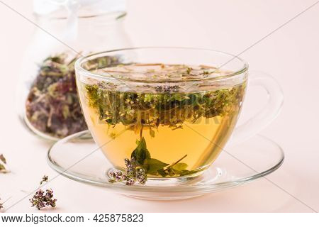 Fresh Hot Tea With Oregano In A Cup And Dry Herb In A Jar. Herbal Medicine And Alternative Therapy.
