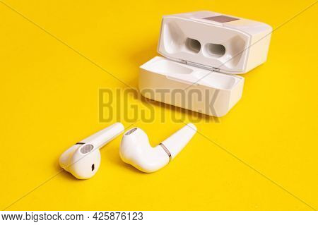 Wireless Earbuds On A Yellow Background Close Up