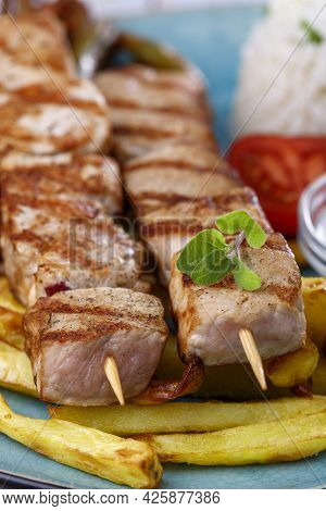 Greek Souvlaki Skewers With French Fries On A Plate