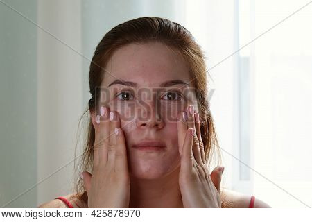 Dissatisfied Woman Touching Face Skin Front Bathroom Mirror. Young Woman Discontented Complexion Ski