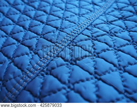 Blue Synthetic Quilted Raincoat Fabric Close-up. Machine Stitches Are Sewn In Several Directions To