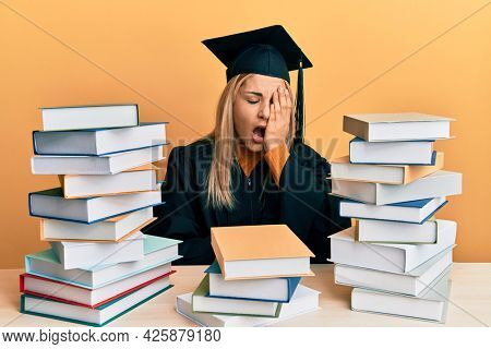 Young caucasian woman wearing graduation ceremony robe sitting on the table yawning tired covering half face, eye and mouth with hand. face hurts in pain.