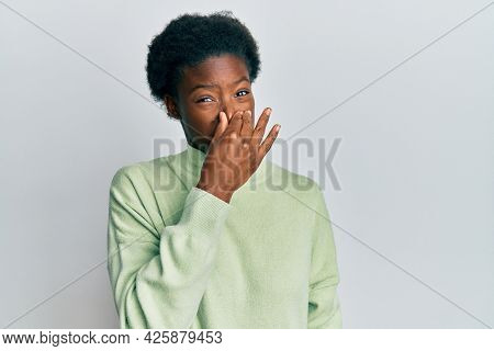 Young african american girl wearing casual clothes smelling something stinky and disgusting, intolerable smell, holding breath with fingers on nose. bad smell