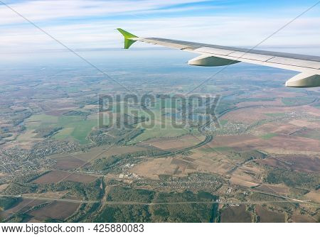 View From The Airplane Window At A Beautiful Blue Sunrise And The Airplane Wing In Clear Sky. Earth