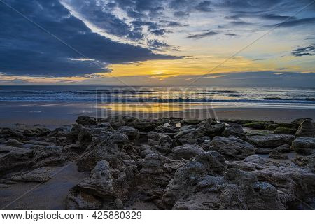 Sunrise Glowing Golden Light Through A Cloudy Sky Over The Atlantic Ocean With A Coquina Rock Covere