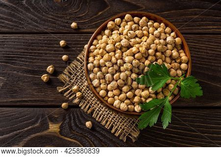 Raw Chickpea Beans In A Wooden Bowl Over Black Wooden Table. Dry Ingredient For Hummus And Healthy V