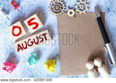 August 5. Date Of August Month. Number Cube With A Flower And Notebook On Diamond Wood Table For The