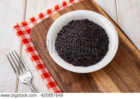 Raw Dry Black Rice Grains In A White Ceramic Bowl On A Brawn Wooden Cutting Board Over Wooden Table.