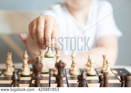 Close-up Of A Chess Piece In The Hands Of A Child. Pawn Move. Game Of Chess. Chess Tournaments And S