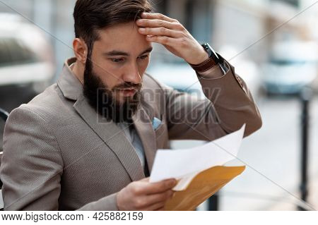 Big Debt Alert. A Shocked Man Reads A Court Letter. Death Of A Loved One, Increased Mortgage Payment