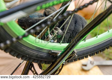 Bike Mechanic Man Repairs Bicycle In Bicycle Repair Shop, Outdoor. Hand Of Cyclist Bicyclist Examine