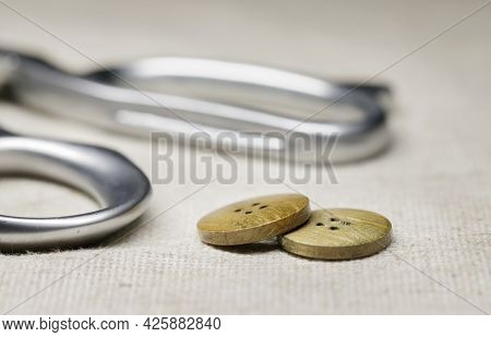 Tailors Scissors Lie On A Burlap Close-up And Wooden Buttons.