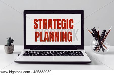A Scrap Of Blue Paper With Clips On A Gray Background With The Text - Strategic Planning.