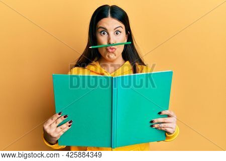 Funny hispanic woman reading a book doing crazy gesture with pencil over mouth like mustache, playful and positive on free time, lazy student