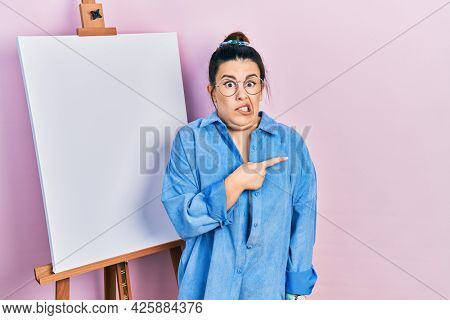 Young hispanic woman standing by painter easel stand pointing aside worried and nervous with forefinger, concerned and surprised expression