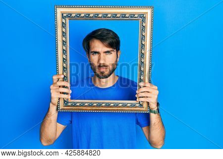 Young hispanic man holding empty frame skeptic and nervous, frowning upset because of problem. negative person.