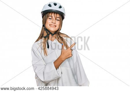 Teenager caucasian girl wearing bike helmet cheerful with a smile of face pointing with hand and finger up to the side with happy and natural expression on face