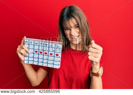 Teenager caucasian girl holding heart calendar annoyed and frustrated shouting with anger, yelling crazy with anger and hand raised
