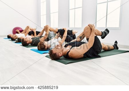 Group of young sporty people concentrate stretching at sport center.