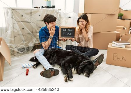 Young caucasian couple with dog holding our first home blackboard at new house laughing and embarrassed giggle covering mouth with hands, gossip and scandal concept