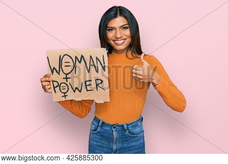 Young latin transsexual transgender woman holding woman power banner smiling happy and positive, thumb up doing excellent and approval sign
