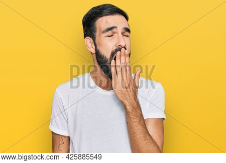 Young hispanic man wearing casual white t shirt bored yawning tired covering mouth with hand. restless and sleepiness.
