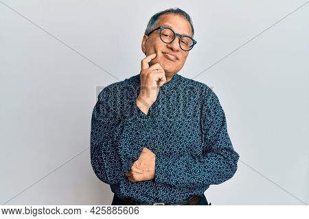 Middle age indian man wearing casual clothes and glasses thinking concentrated about doubt with finger on chin and looking up wondering