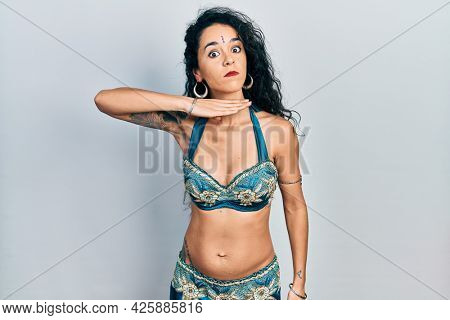 Young woman wearing bindi and traditional belly dance clothes cutting throat with hand as knife, threaten aggression with furious violence