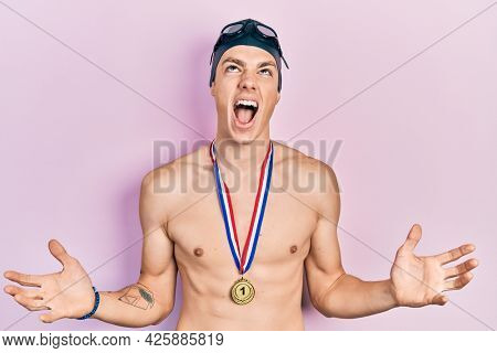 Young hispanic man wearing swimmer glasses and gold medal crazy and mad shouting and yelling with aggressive expression and arms raised. frustration concept.