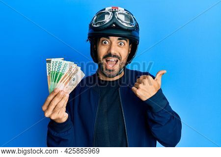 Young hispanic man wearing motorcycle helmet holding south korea won pointing thumb up to the side smiling happy with open mouth