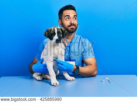 Handsome hispanic veterinary man with beard checking dog health using stethoscope smiling looking to the side and staring away thinking.