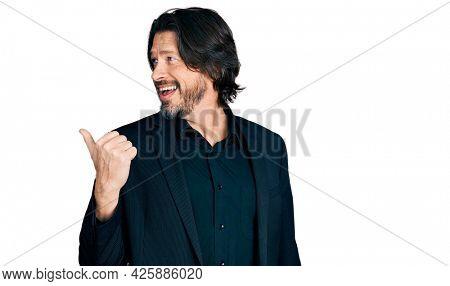 Middle age caucasian man wearing business clothes pointing thumb up to the side smiling happy with open mouth