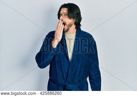 Middle age caucasian man wearing bathrobe and glasses bored yawning tired covering mouth with hand. restless and sleepiness.