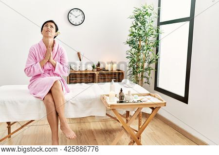 Beautiful caucasian woman wearing bathrobe at wellness spa begging and praying with hands together with hope expression on face very emotional and worried. begging.