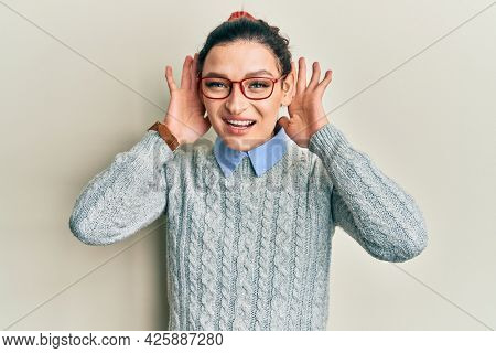 Young caucasian woman wearing casual clothes and glasses trying to hear both hands on ear gesture, curious for gossip. hearing problem, deaf