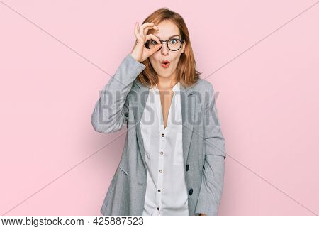 Young caucasian woman wearing business style and glasses doing ok gesture shocked with surprised face, eye looking through fingers. unbelieving expression.