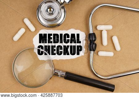 Medicine And Health Concept. On The Table Is A Stethoscope, Pills, A Magnifying Glass And Paper With