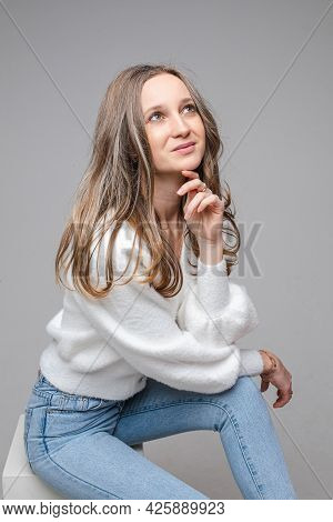 Portrait Of Young Dreamy Long-haired Caucasian Girl In White Sweater And Blue Jeans On Gray Studio B