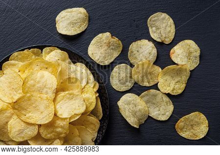 Top View On A Crunchy Potato Chips On A Black Ceramic Plate Over Black Slate Surface. Tasty Snack Of
