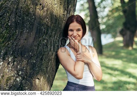 A Girl With A Bob Hairstyle Caucasian Walks In A City Park And Smiles.