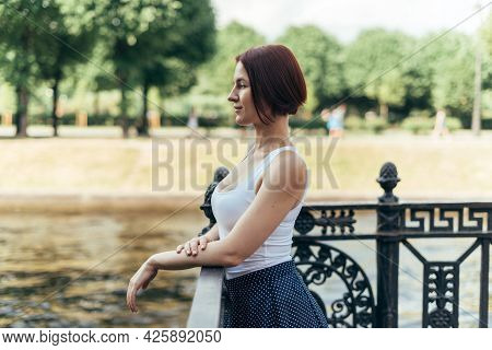 A Girl With A Bob Hairstyle Caucasian Walks In A City Park On The Bridge And Looks To The Side.