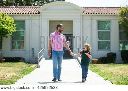 American Father And Son Walking Trough School Park. Parent Taking Child To School. Pupil Of Primary