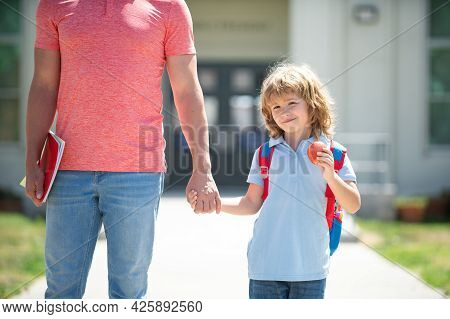 Teacher In T-shirt And Cute Schoolboy With Backpack Near School Park. Kid Elementary Student Carryin
