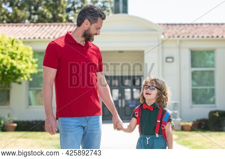 Outdoor School. American Father And Son Walking Trough School Park.
