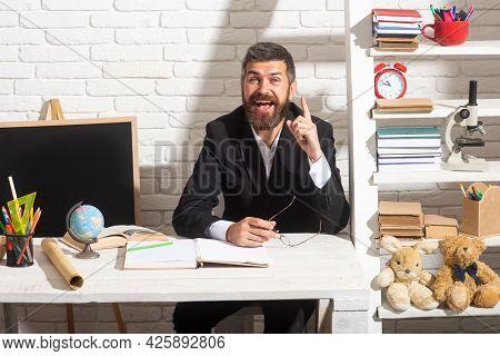 Portrait Of Male Teacher From Preschool Or Elementary School In Class. Teacher Having Idea. Amazed T